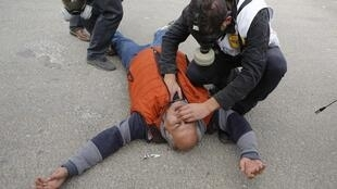 Bác sĩ cứu chữa một nhà báo bị trúng hơi cay trong một cuộc biểu tình ở Bêlem, Palestine, 23/12/2014.