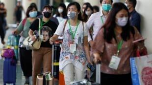Des passagers portant des masques au terminal des arrivées internationales de l'aéroport Gusti Ngurah Rai sur l'île de Bali, en Indonésie, le 4 février 2020.