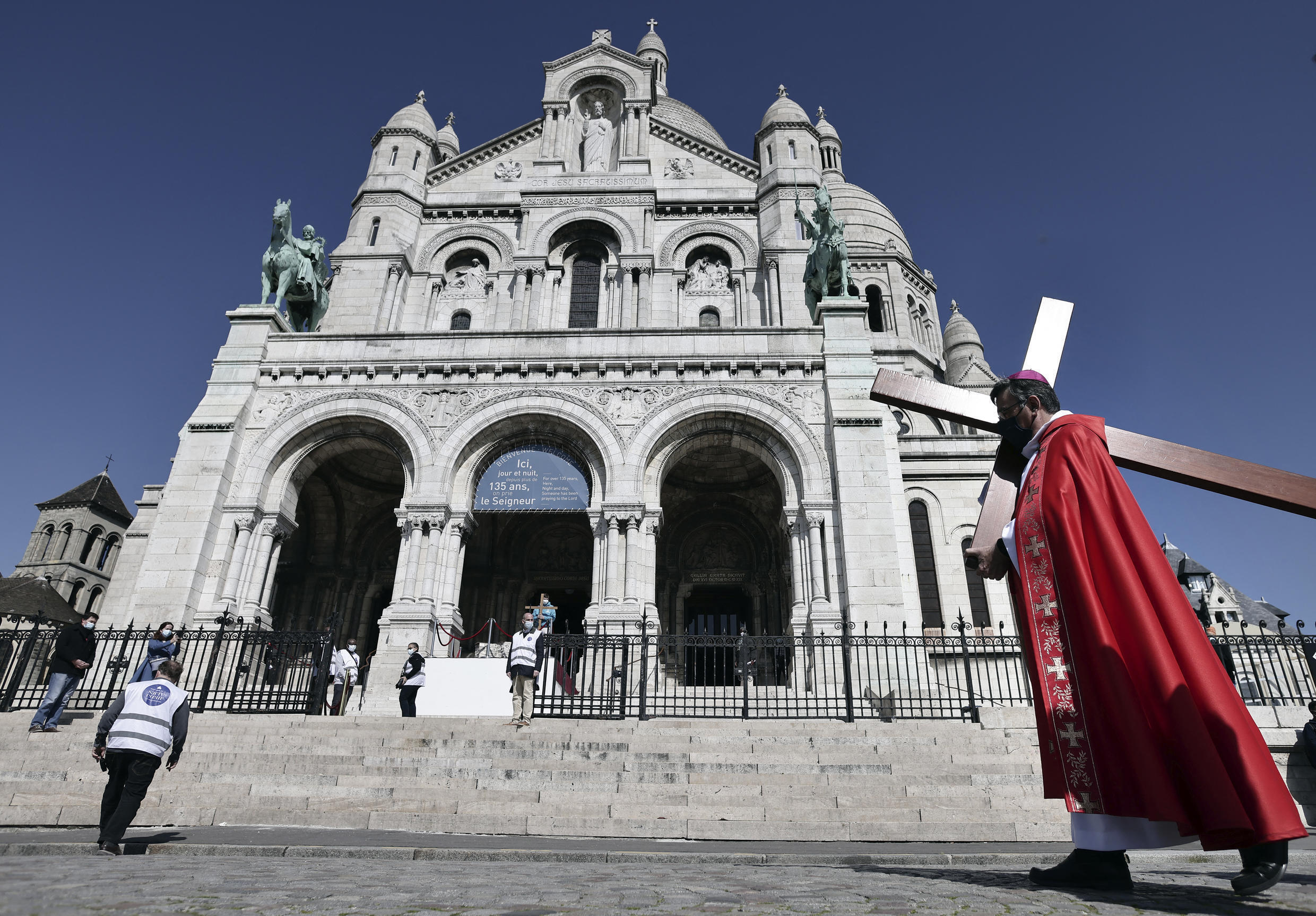 Archbishop of Paris Michel Aupetit carries the holy cross during Good Friday celebrations at the Sacre Coeur Basilica in Paris on April 2, 2021.