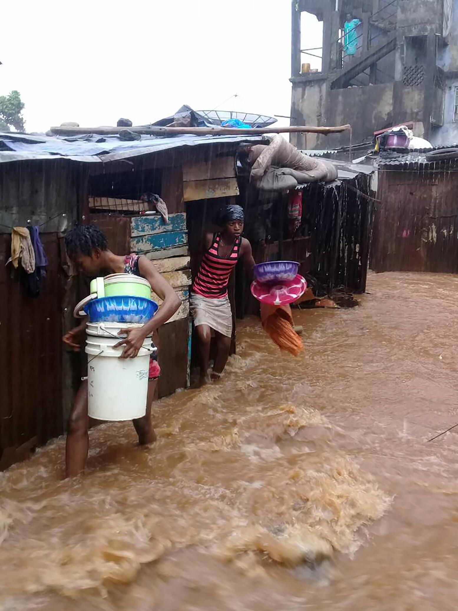 Wakazi wa eneo la Regent wakijaribu kukimbia kabla ya maporomoko, Jumatatuhii, Agosti 14, nje kidogo ya mji wa Freetown.