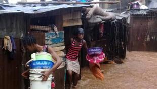 Des habitants de Regent tentent de fuir devant l'avancée de la coulée de boue, ce lundi 4 août dans la banlieue de Freetown.