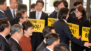 South Korean President Prak Geun-hye (in red) walks past members of the minor opposition Justice Party at the National Assembly in Seoul, South Korea, November 8, 2016