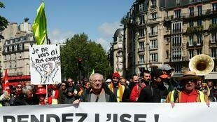 Des «Gilets jeunes» à Paris tiennent une bannière sur laquelle on peut lire «Rendez l'ISF ou la taxe sur la fortune», un appel à abroger la décision du président français l'année dernière de couper l'ISF qui était prélevé sur les hauts revenus.