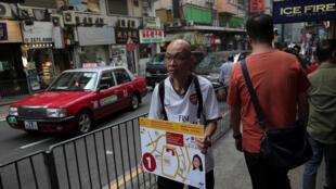 Un homme tient une pancarte indiquant l'emplacement d'un bureau de vote à Hong Kong, le 23 novembre.
