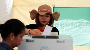 Une femme dépose son bulletin dans l'urne lors des élections législatives cambodgiennes le 29 juillet 2018 à Phnom Penh.