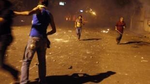 Des protestataires se sauvent pour échapper aux gaz lacrymogènes de la police, sur la place Tahrir, au Caire, dans la nuit de 28 au 29 juin 2011.