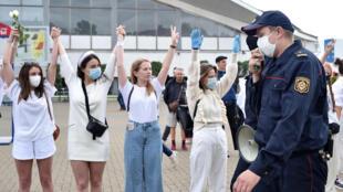 Un policía bielorruso pide a unas manifestantes que se dispersen durante una protesta contra la violencia policial en las manifestaciones opositoras, el 12 de agosto de 2020 en Minsk