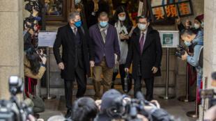 Jimmy Lai (en el centro, con chaqueta morada) sale del tribunal que ordenó su regreso a prisión, el 31 de diciembre de 2020 en Hong Kong