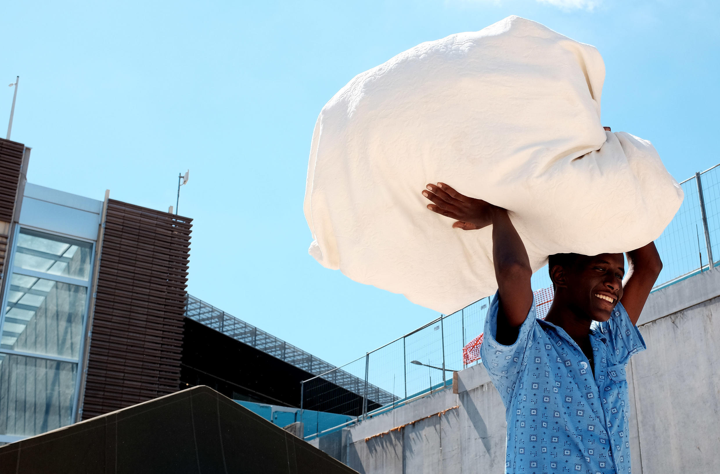 A migrant from Eritrea carries blankets at a refugee camp next to the Tiburtina train station in Rome.