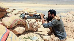 Un miembro de las fuerzas del gobierno yemení respaldado por Arabia Saudí apunta con su arma tras unos sacos terreros en una zona de conflicto con los rebeldes hutíes, el 6 de abril de 2021 en un paraje de la provincia de Marib, al noreste de Yemen