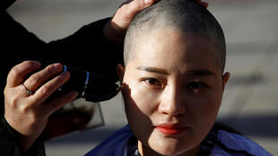 Li Wenzu, the wife of Wang Quanzhang, shaves her head in public to protest against her husband's detention.