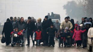 Des habitants d'Alep marchent dans une zone contrôlée par les rebelles.