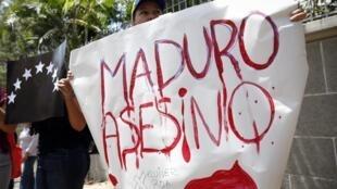 Un manifestante exhibe una pancarta durante una protesta en Caracas, el 25 de febrero de 2015, por la muerte del liceista Kluiverth Roa en San Cristóbal