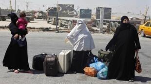 Passageiras palestinas esperam ônibus após fechamento da passagem de Rafah em 15 de agosto de 2013.