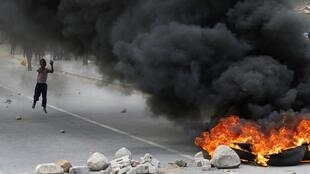 A child runs towards a burning barricade during a strike by farm workers at De Doorns on the N1 highway
