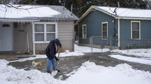 A resident in Waco, Texas clears snow as the oil-rich state struggles to cope with a historic cold snap