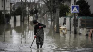 Un résident d'un quartier pavillonnaire de Villeneuve-Saint-Georges, dans le Val-de-Marne, nettoie les débris d'une rue inondée, le 25 janvier 2018.