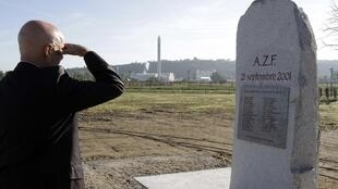 A man stands alone to pay tribute at the stele to the victims of the AZF factory explosion 21 September, 2011.