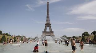 Pessoas a tomarem banho na fonte do Trocadero, em frente à Torre Eiffel, em Paris, a 28 de Junho de 2019.