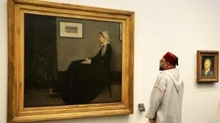 """Moroccan King Mohammed VI looks at a painting titled """"Whistler's Mother"""" by James Abbott McNeill Whistler (1871) at the November 2017 opening of Louvre Abu Dhabi Museum"""