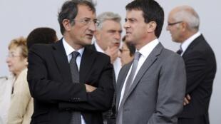 Le ministre de la Ville, François Lamy (G) en pleine discussion avec le ministre de l'Intérieur, Manuel Valls (D), lors du défilé du 14 juillet 2012 à Paris.