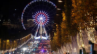 Christmas holiday lights hang from trees to illuminate Champs Elysees avenue in Paris as rush hour traffic fills the avenue leading down to the Giant Ferris Wheel at place de la Concorde in Paris, France, November 21, 2016.