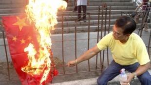 Ativista filipino coloca fogo em bandeira chinesa durante protesto nesta terça-feira.