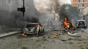 Des voitures en feu sur le lieu de l'explosion, à Mogadiscio, le 30 juillet 2017.