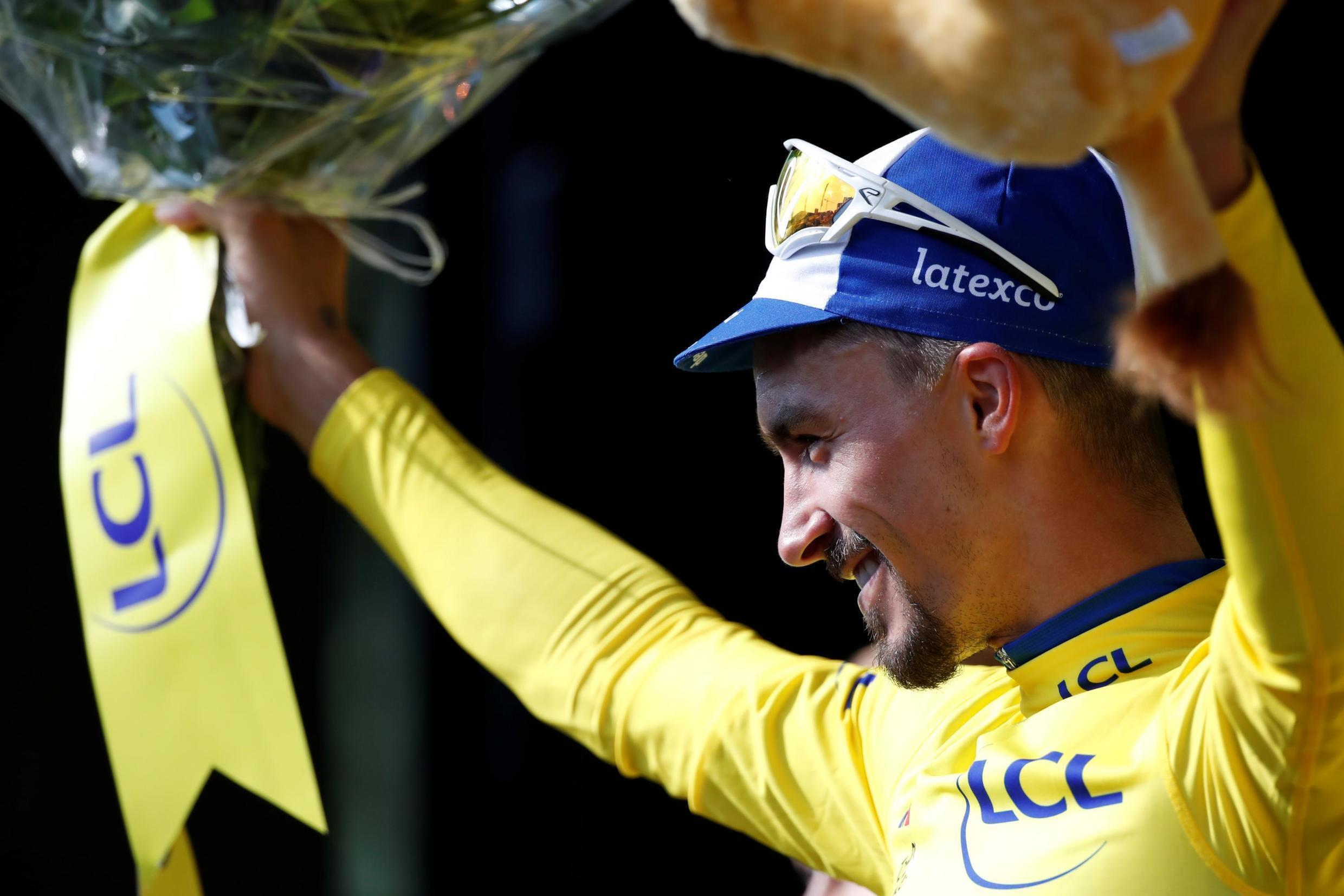 French rider Julian Alaphilippe celebrates on the podium, wearing the yellow jersey on 13 July 2019.