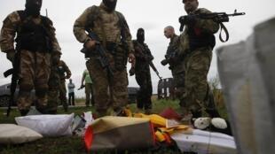 Des miliciens séparatistes à proximité de débris de l'avion abattu au-dessus de l'est de l'Ukraine, jeudi 17 juillet 2014.