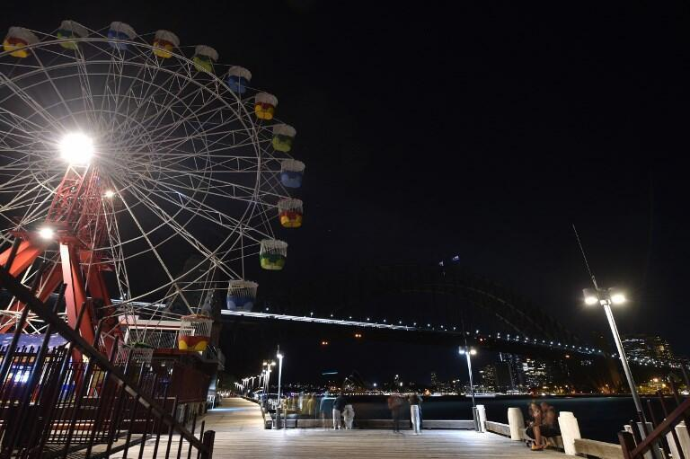 The Sydney Harbour Bridge, the Opera House and the ferris wheel are seen after their lights went out as seen from Sydney's Luna Park for the Earth Hour environmental campaign on 30 March, 2019.