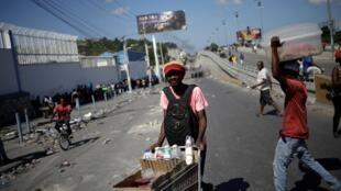 Un vendeur de rue en marge d'une manifestation à l'appel des syndicats des travailleurs du textile, le 28 octobre à Port-au-Prince.