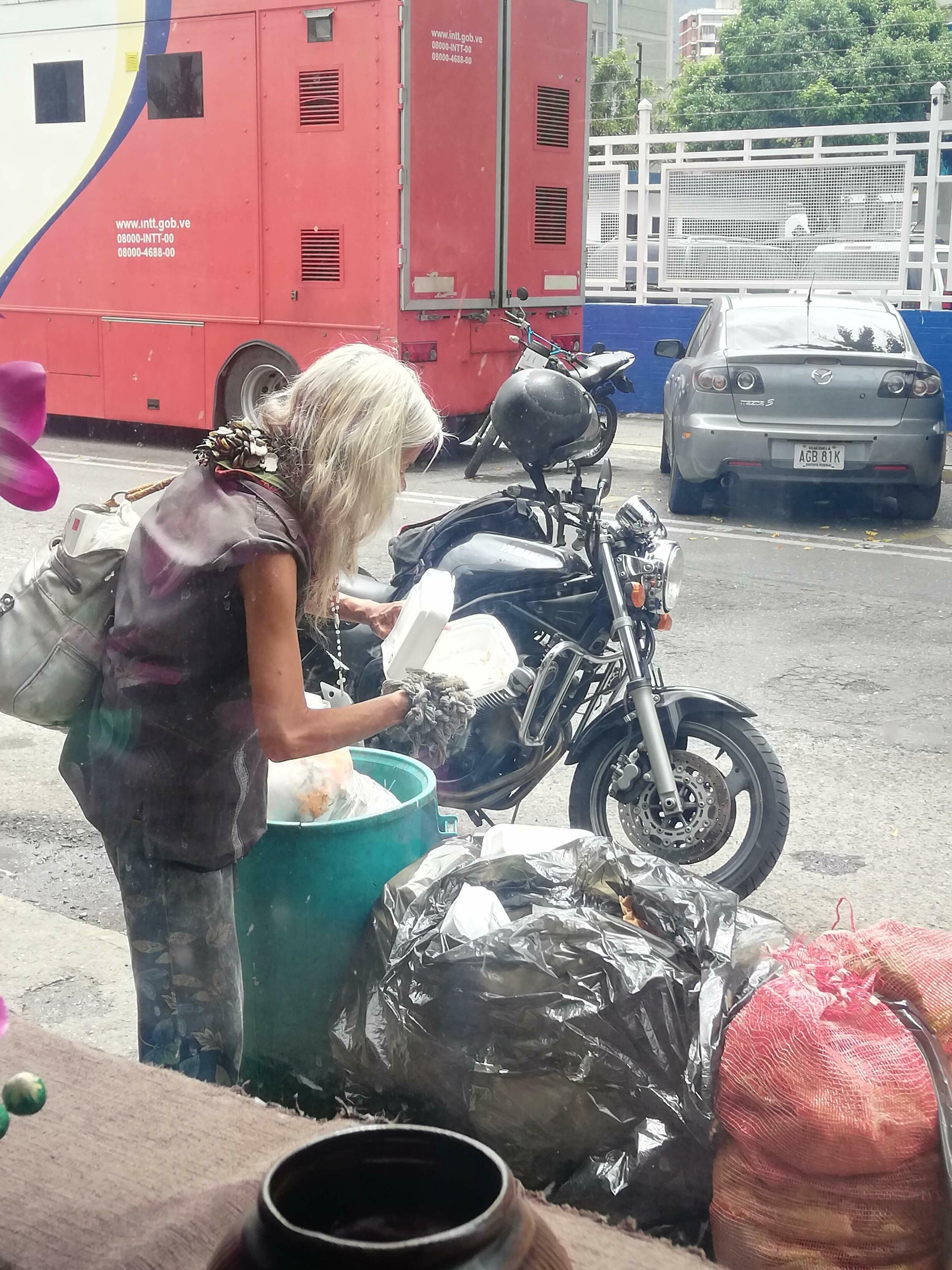 Idosa revira lixo em Caracas à procura de alimentos.