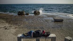 Un migrante duerme en una playa de la isla griega de Lesbos, 3 de marzo de 2020 (foto de ilustración).