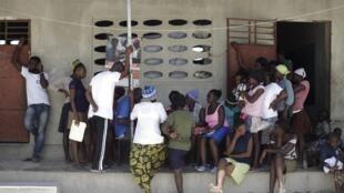 Des personnent attendent leur tour pour s'entretenir avec un agent de l'Organisation internationale pour les migrations dans un camp pour Haïtiens et Haïtiens-dominicains à Malpasse, à la frontière entre les deux pays, le 3 août 2015.