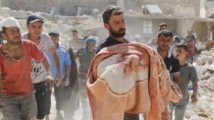 Evacuation d'un corps à Alep en Syrie après un lâcher de barils d'explosifs par le régime, le 30 septembre 2014.