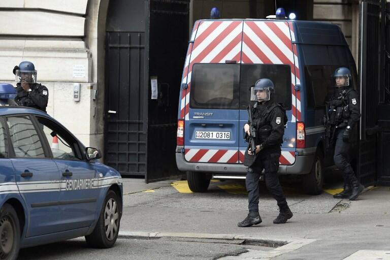 Armed policemen stand guard upon the arrival of a van of the penitentiary authorities, on 2 October, 2017 at Paris court house, before the opening of the trial of Abdelkader Merah.