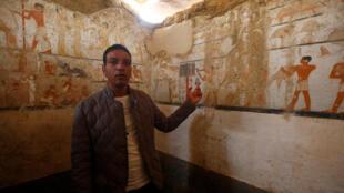 Un guía del Ministerio de Antigüedades muestra las pinturas murales de la tumba de Hetpet.