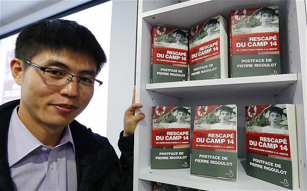 Shin Dong-hyuk devant son livre «Rescapé du camp 14».
