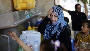 Des Palestiniens remplissent des bidons à une fontaine publique, le samedi 19 juillet 2014. La grande majorité de la population est privée d'un accès suffisant à l'eau dans la bande de Gaza.