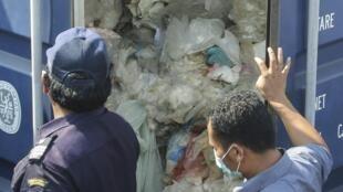Le 29 juillet 2019, à Batam en Indonésie, les douanes en pleine inspection d'un conteneur de déchets qui sera renvoyé à l'expéditeur. Jakarta a renvoyé sept conteneurs cette semaine vers Hong Kong et la France, les considérant illégaux.