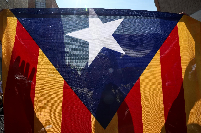Жители Каталонии несут каталонский флаг на митинге в поддержку референдума о независимости,19 сентября 2017 года.