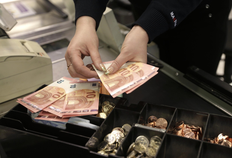Кассир считает 10-евровые купюры перед открытием магазина в Вильнюсе, Литва, 1 января 2015 г.