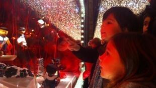 Os irmãos Helena e Louis admiram a vitrine do Printemps Haussmann, em Paris.