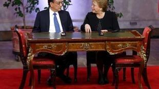 El anuncio fue realizado este lunes durante una visita oficial a Santiago  del primer ministro de China, Li Keqiang, aquí junto a la presidenta chilena Michelle Bachelet.