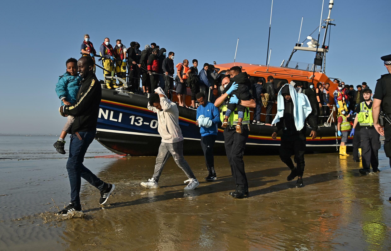 Un grupo de migrantes, algunos con niños, es escoltado tras ser recogido por un barco de los salvavidas británicos cuando cruzaban el Canal de la Mancha, el 7 de septiembre de 2021 en una playa de Dungeness, Inglaterra