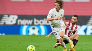 Luka Modric trata de sortear la entrada de Óscar de Marcos durante el partido liguero entre el Athletic de Bilbao y el Real Madrid disputado el 16 de mayo de 2021 en el estadio de San Mamés, en la ciudad vasca de Bilbao
