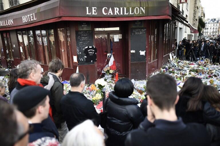 People observe a minute of silence on 16 November in front of the Le Carillon cafe in Paris.