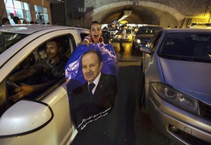 Menino agita cartaz da campanha de Abdelaziz Bouteflika, reeleito para um quarto mandato presidencial.