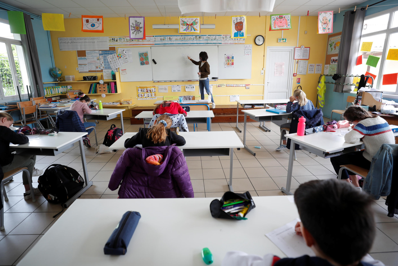 A teacher, wearing a protective face mask, teaches schoolchildren at a private school in Saint-Sebastien-sur-Loire near Nantes, France.